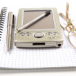 Pen, PDA and eyeglasses on notebook — Stock Photo
