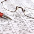 Stock Photo: Pen and glasses on financial report