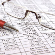 Pen and glasses on financial report — Stock Photo #1143015