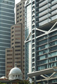 Old building among modern skyscrapers — Stock Photo