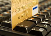 Gold credit card on computer keyboard — Stock Photo