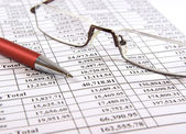 Pen and glasses on financial report — Stock Photo