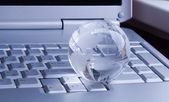 Globe on keyboard of modern notebook — Stock Photo