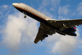 Passenger airplane taking off in blue sk — Stock Photo