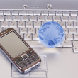 Mobile phone and glass globe on laptop — Stock Photo #2188957