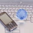 Stock Photo: Mobile phone and glass globe on laptop