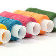 Color thread reels over white background — Stock Photo