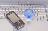 Mobile phone and glass globe on laptop — Stock Photo