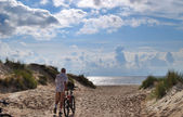 Man with bicycle go to seacoast — Stock Photo