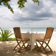 Table and chairs on a beach - Stock Photo