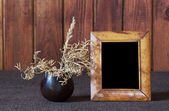 Ikebana and old photo frame — Stock Photo