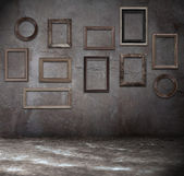 Grunge room with wooden frames — Stock Photo