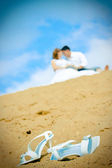 Bride shoes and newly married couple — Stock Photo