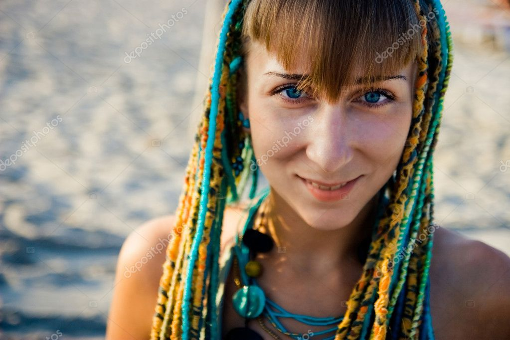 Beautiful young ethnic style woman with blue eyes, multicolored braids at the beach, looking at camera, shallow depth of field — Stock Photo #1184281