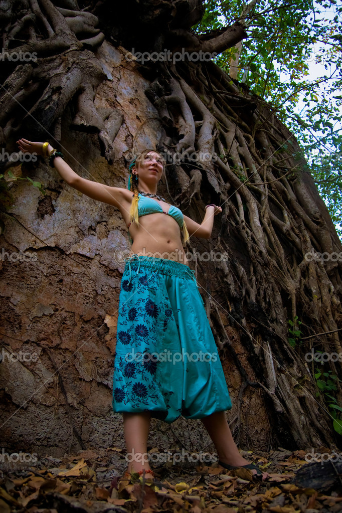 Beautiful woman wearing blue pants and bikini with arms like Shiva standing near an old wall and Banyan Tree's roots. Redi fort, India. View from below. — Stock Photo #1288662