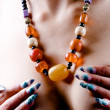 Amber necklace and artistic manicure - Stock Photo