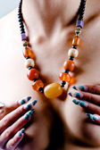 Amber necklace and artistic manicure — Stock Photo