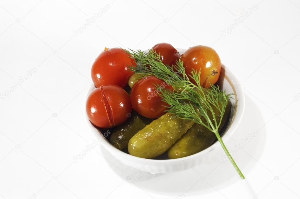Canned tomatoes and cucumbers in a bowl with a sprig of dill isolated on a white background — Stock Photo #1771787