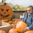 The woman chooses a pumpkin on Halloween — Stock Photo
