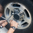 Repair machine. Replacement wheel. Man - Stock Photo