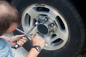 Repair machine. Replacement wheel. Man — Stock Photo