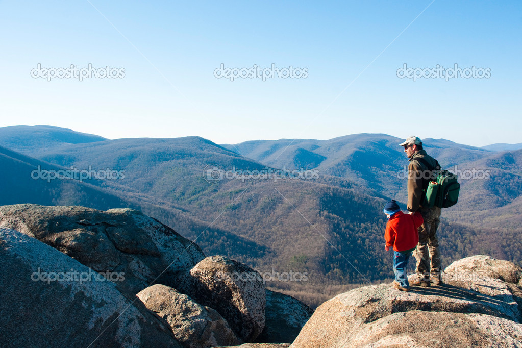 Father and son on a mountain top opened up admiring the view  Stock Photo #1158915