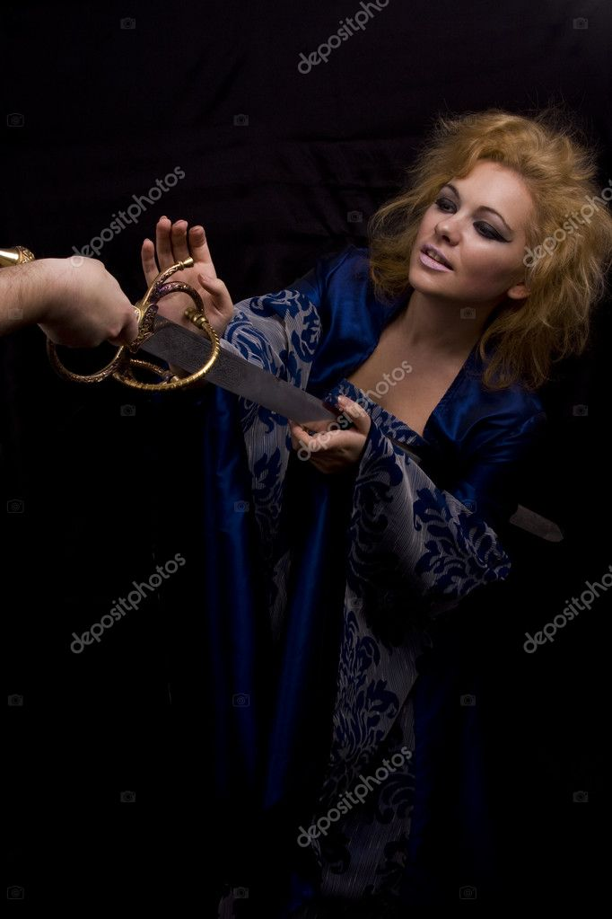 Woman in medieval  dress die of weapon. Man kill horrible witch with sword on black background.  — Stock Photo #1158939