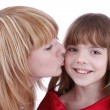 Mother is kissing her happy daughter. - Stock Photo