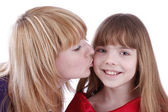 Mother is kissing her happy daughter. — Stock Photo