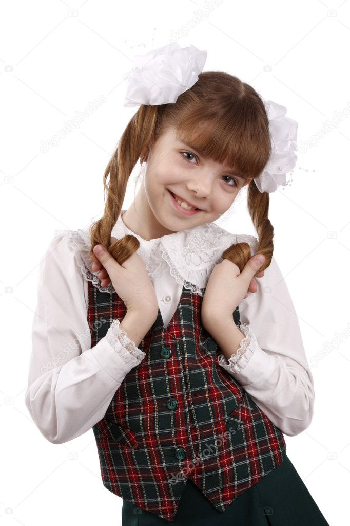 Little girl in school uniform. Pupil is trifling with hair. Isolated on white in studio.  Stock Photo #1166908