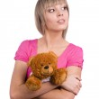 Girl in pink dress holding teddy bear — Stock Photo
