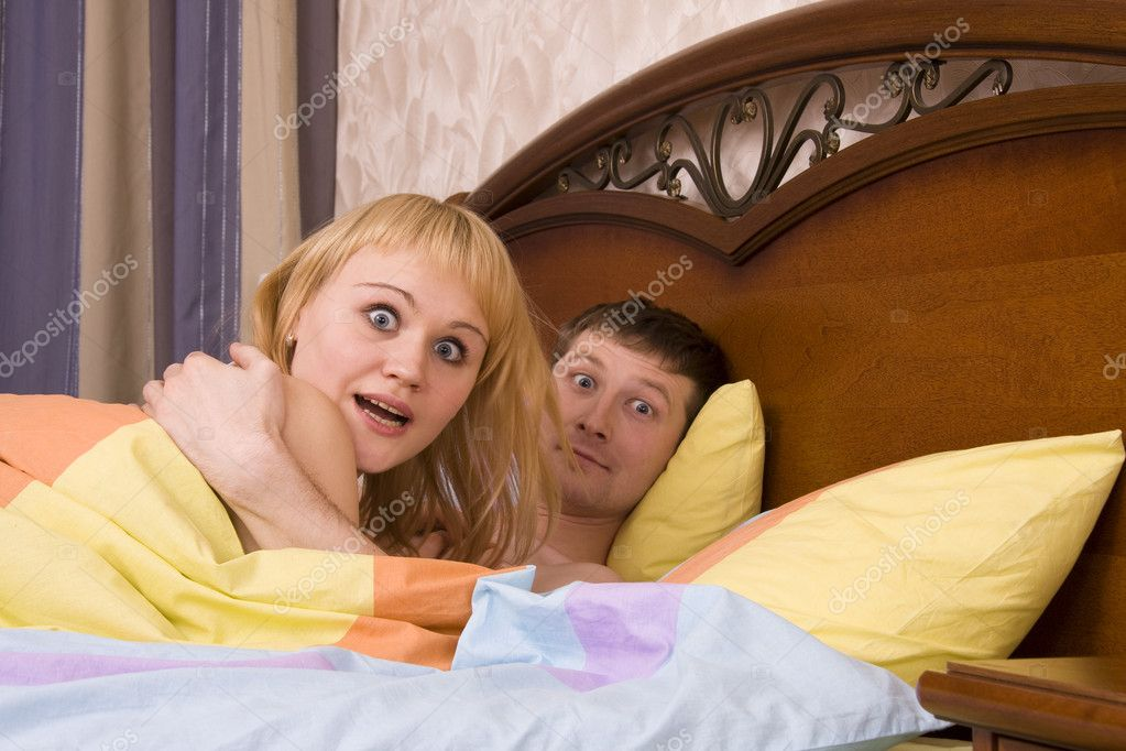 sexy man looking at woman snoring in bed