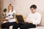 Vrouw vertoornd man voor werkende laptop — Stockfoto
