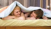 Lyckliga paret spelar i sängen — Stockfoto
