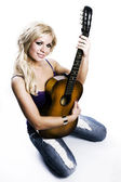 Blonde Girl sitting with guitar — Stock Photo