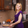 Woman cutting hot apple pie at kitchen — Stockfoto