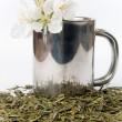 Stock Photo: Cup of tea with flower and tea leafs