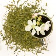 Cup of tea with flower and tea leafs — Stock Photo