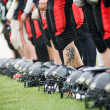 Stock Photo: Row of football helmets and feet