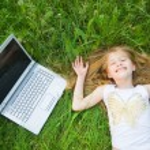 rolig liten flicka med laptop — Stockfoto