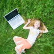 Funny little girl with laptop outside — Stock Photo