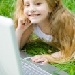 Smiling little girl with laptop — Stock Photo