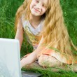 Funny little girl sitting with laptop ou — Stock Photo