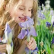 Little girl smelling flower — Stock Photo