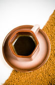 Cup of black coffee on coffee grounds — Stock Photo