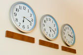 Row of clocks with different time — Stock Photo