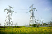 Two electrical towers on blue sky backgr — Stock Photo