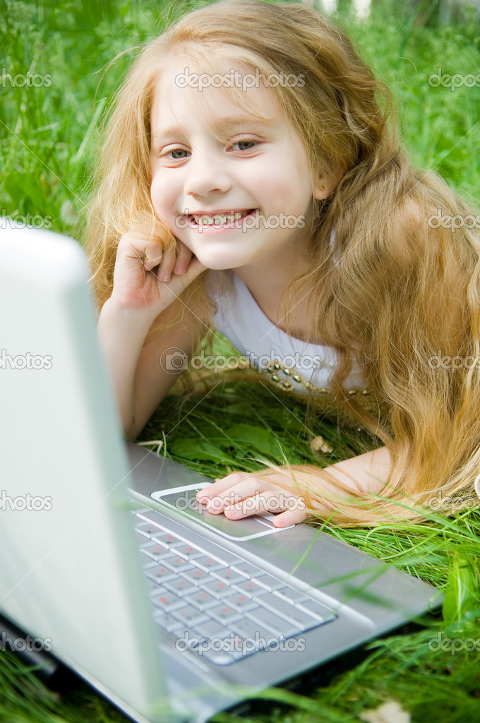 Smiling little girl with laptop in green grass — Stock Photo #1243707