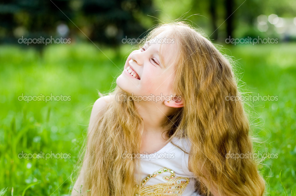 Smiling little girl in green grass — Zdjęcie stockowe #1249796
