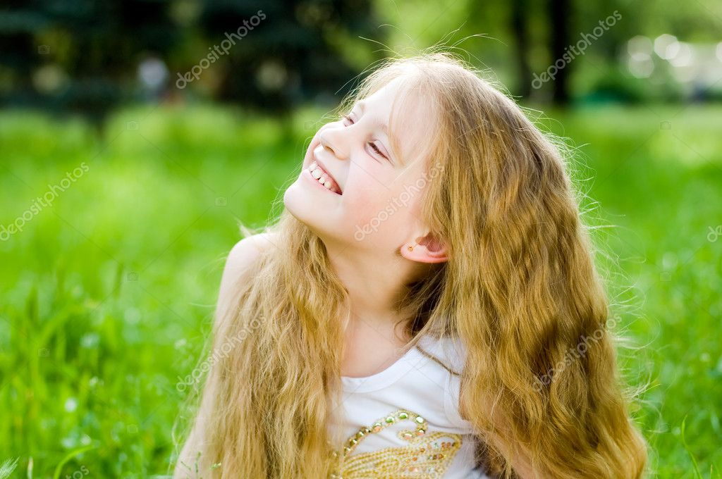 Smiling little girl in green grass — Photo #1249796